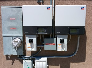 A pair of SMA Sunny Boy string inverters next to the net meter (left).